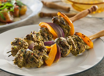 Lamb tikka kebabs with spiced tomatoes and raita