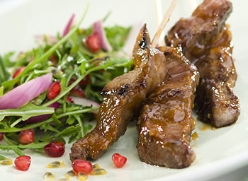 Sticky apricot lamb kebabs with passion fruit, rocket and pomegranate